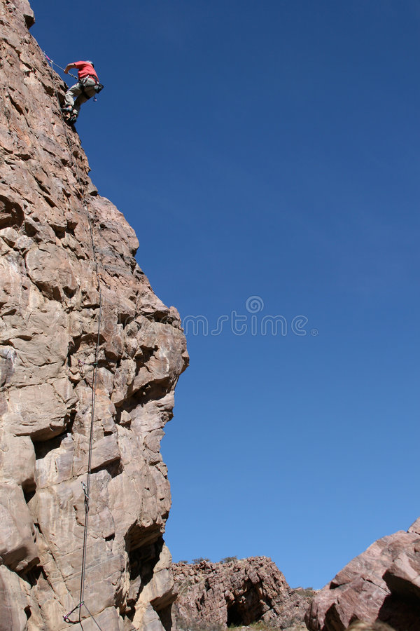 登山人rappeling的岩石 库存图片