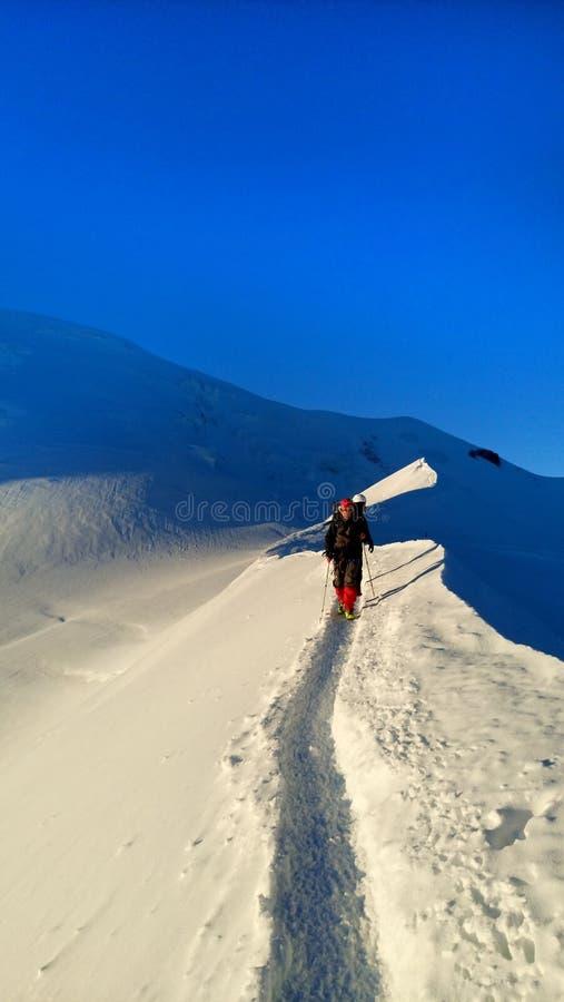 登山家到达一座多雪的山的顶层 库存照片