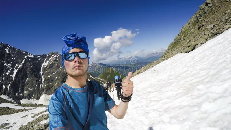 登山家到达一座多雪的山的顶层 免版税库存图片