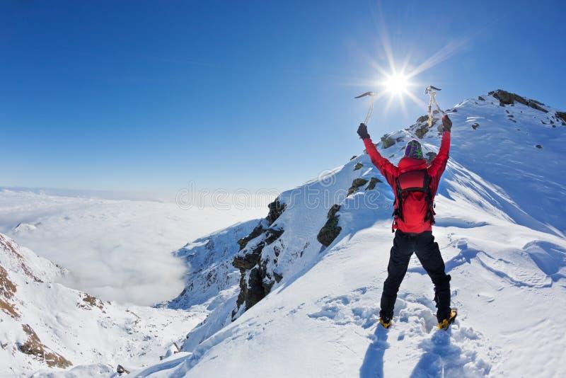 登山家到达一座多雪的山的顶层 免版税库存照片