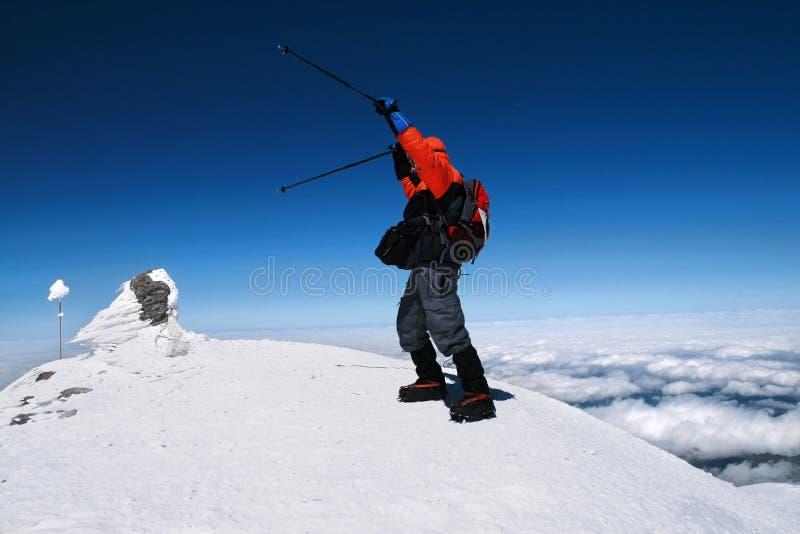 登山家在一个晴朗的冬日到达一座多雪的山的上面 r 免版税库存照片
