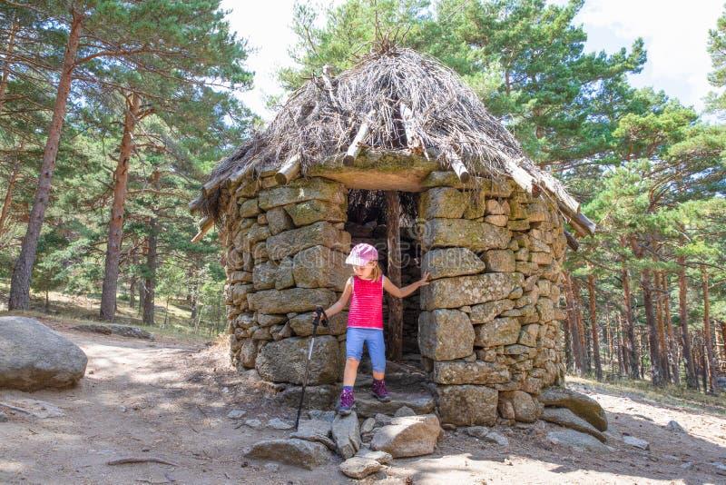 登山家小孩用在古老石小屋的迁徙的棍子在卡嫩西亚森林里 库存图片