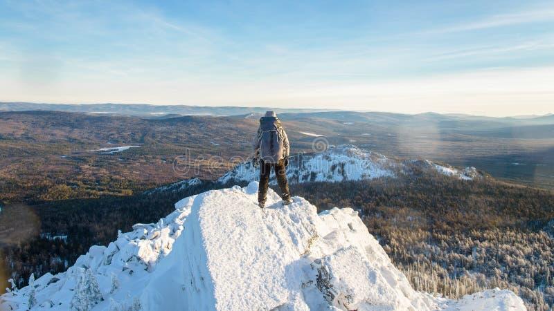 登山家攀登了山上面、人远足者站立在岩石峰顶的报道用冰和雪,看法从 免版税库存照片