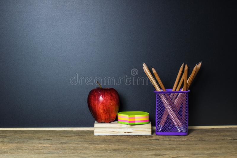 登记概念教育查出的老 红色苹果,柱子,在木桌上的铅笔 免版税库存照片