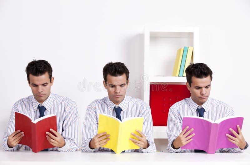 登记读三孪生的生意人 免版税库存图片