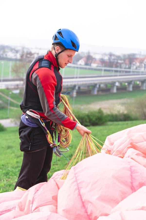 登陆的年轻男性滑翔伞培养从地面的降伞 免版税库存图片