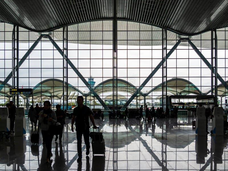 白云队,广州,中国- 2019年3月10日–进入白云队国际性组织的离开大厅剪影观点的旅行家 免版税库存照片