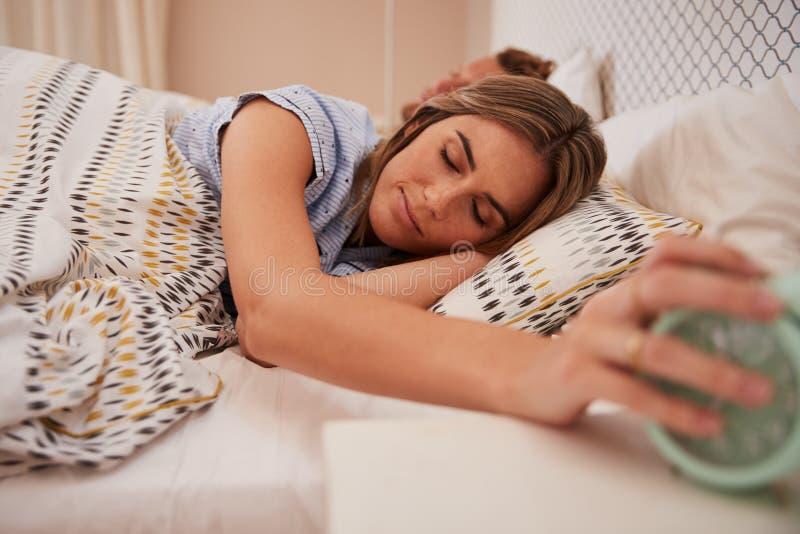 白人妇女一半睡着在床上为闹钟,睡觉在背景,关闭中的伙伴提供援助  库存图片