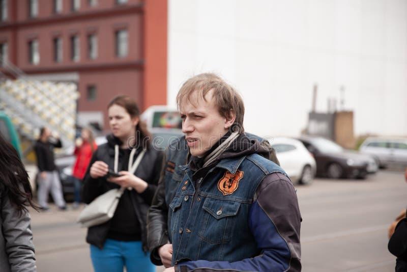 白俄罗斯,米斯克,可以17日2015年,Oktyabrskaya街道,骑自行车的人节日 在城市街道上的殷勤年轻人身分 免版税库存照片