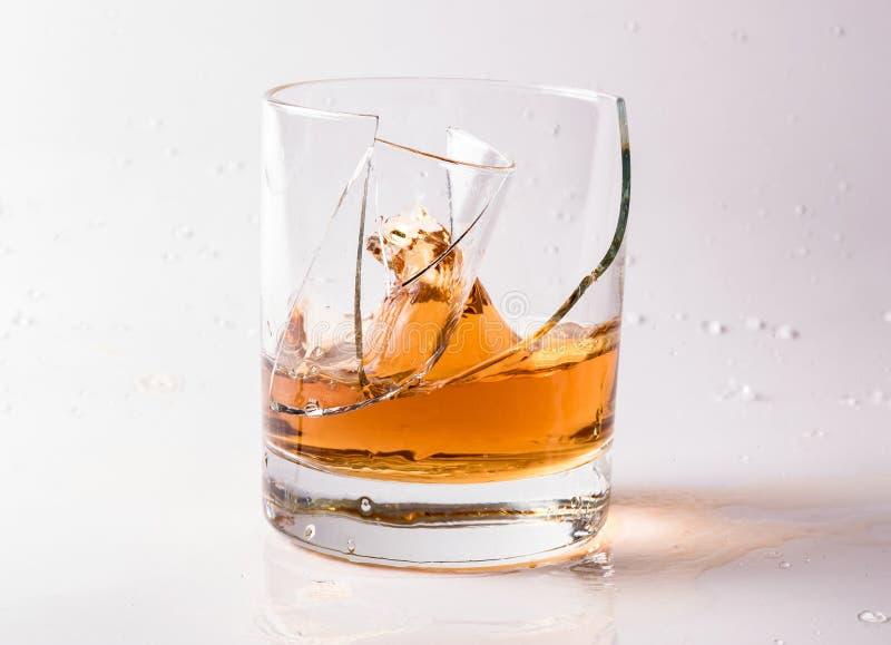 白兰地酒或白兰地酒一块破碎玻璃 玻璃碎片和飞溅饮料图片