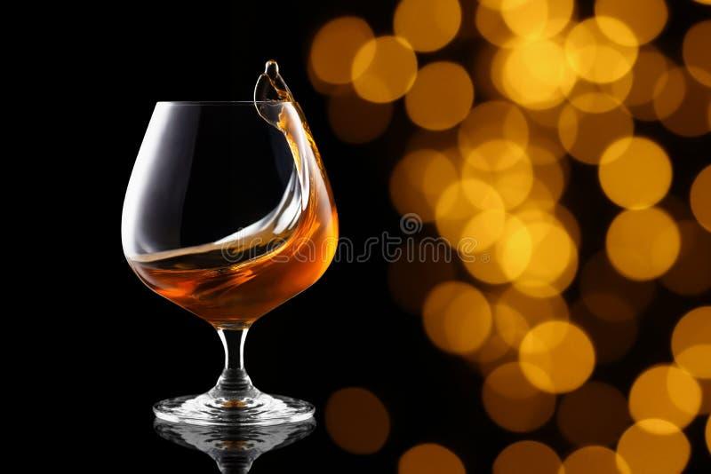 白兰地酒飞溅在一口威士忌酒玻璃的 库存照片