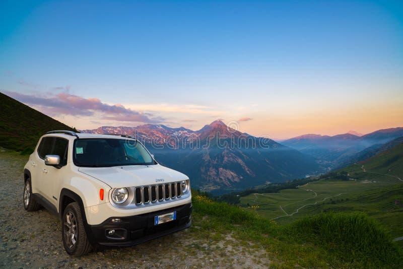 白吉普叛教者在土路从上面停放了在意大利阿尔卑斯的全景点 在日落的五颜六色的天空,在Th的薄雾 免版税库存图片