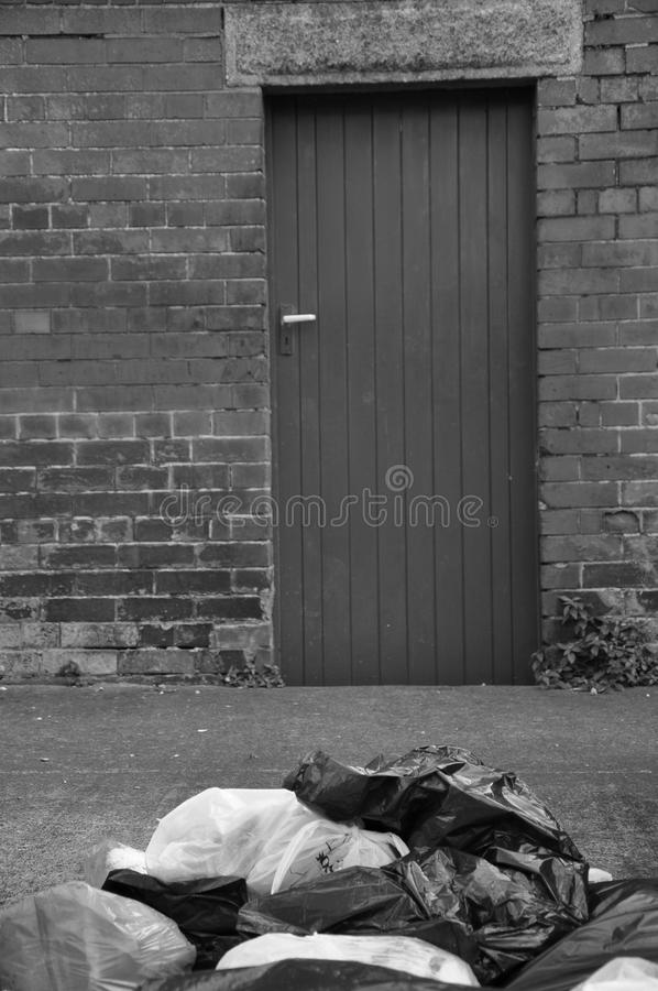 黑白垃圾被倾销对砖墙 库存图片