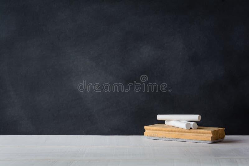 白垩和橡皮擦在白色书桌上上 黑板背景 免版税库存照片