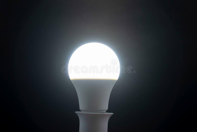 白天铅白在黑背景的电灯泡 免版税库存照片