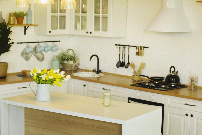 白昼时,大白桌和黄花的明亮厨房。白昼明亮的厨房,上面有大白桌和黄花 免版税库存图片