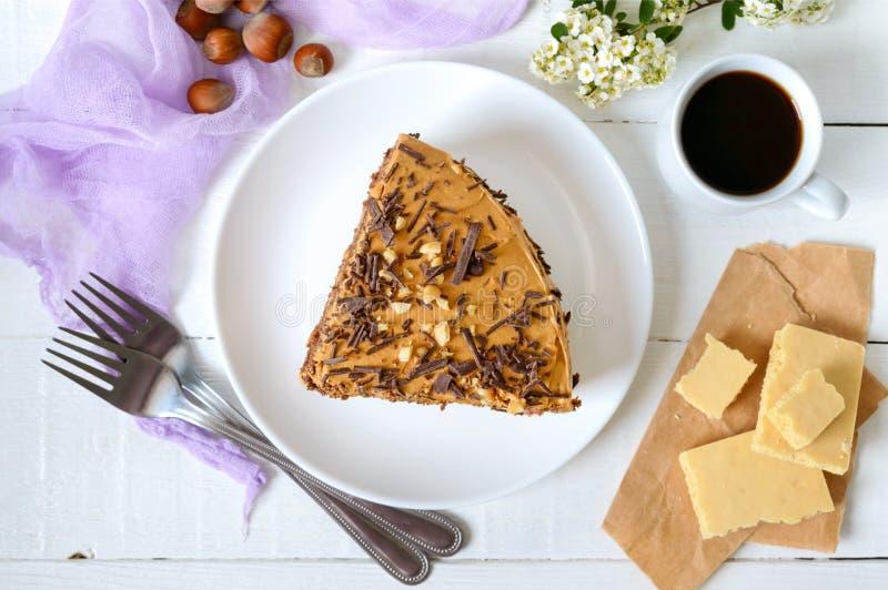 白木桌上加坚果奶油的巧克力蛋糕 一块蛋糕和一杯咖啡 顶视图 免版税图库摄影