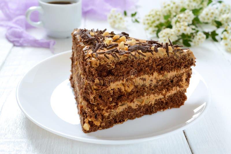 白木桌上加坚果奶油的巧克力蛋糕 一块蛋糕和一杯咖啡 库存照片