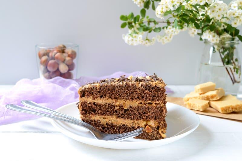 白木桌上加坚果奶油的巧克力蛋糕 一块蛋糕和一杯咖啡 免版税库存图片