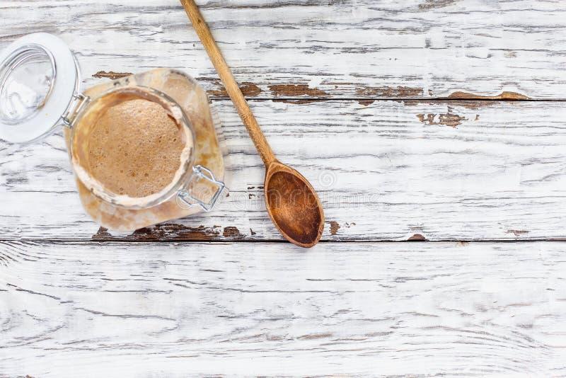 白木背景上健康的全麦酸面团发酵剂 免版税库存照片
