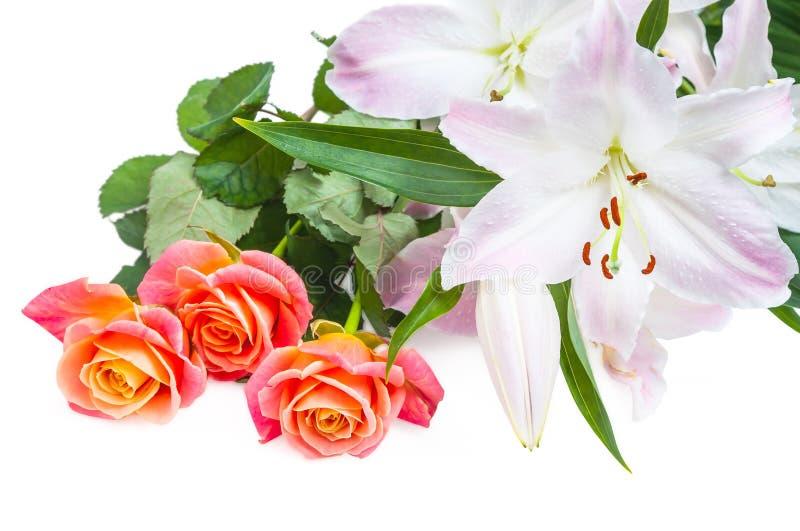 白桃红色百合和三朵红橙色玫瑰在白色背景 免版税库存图片