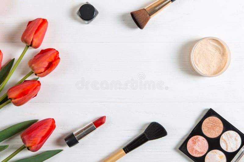 白桌上的红郁金香和化妆品,空白 复制空间 库存照片