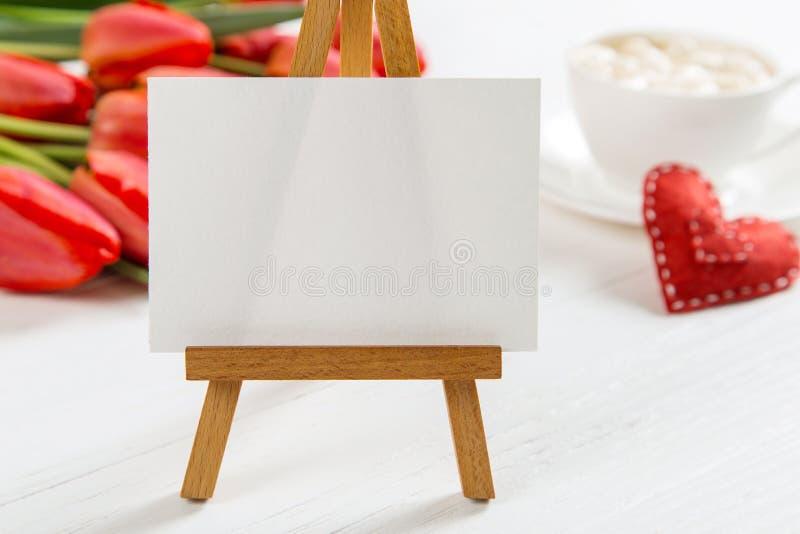 白桌上红郁金香、红心和咖啡杯背景的标志 准备母亲日贺卡 复制 图库摄影