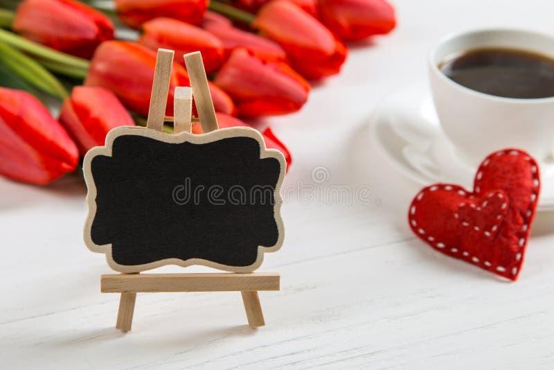 白桌上红郁金香、红心和咖啡杯背景的黑色标牌 准备母亲日贺卡 库存图片