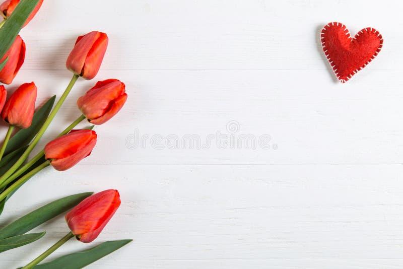 白桌红郁金香红心,明信片背景空白 复制空间 免版税库存图片