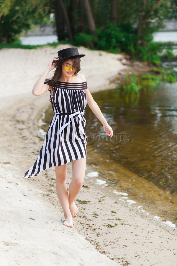 黑白海滩装的走豪华旅行的妇女采取在沙子夏天海滩的漫步 女孩游人在夏天 库存照片