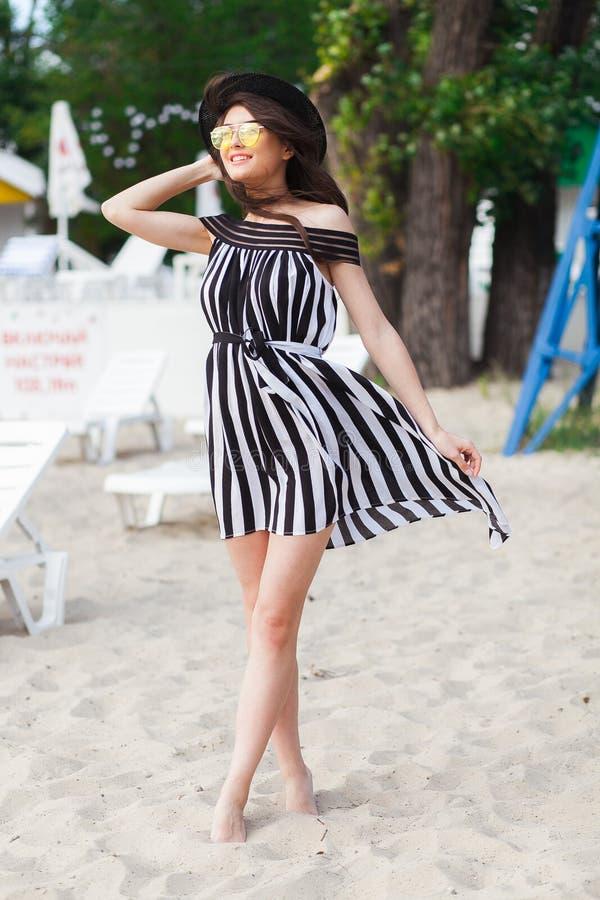 黑白海滩装的走豪华旅行的妇女采取在沙子夏天海滩的漫步 女孩游人在夏天 免版税图库摄影