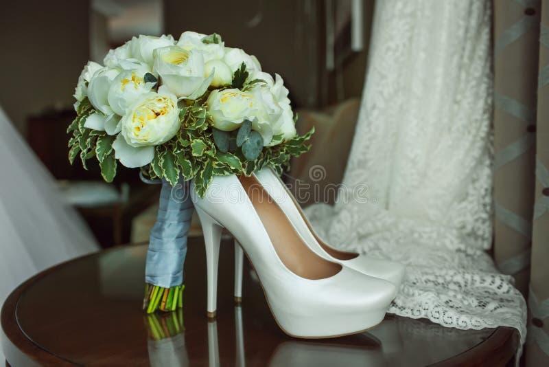 白玫瑰和典雅的婚礼鞋子花束在木桌上 库存照片
