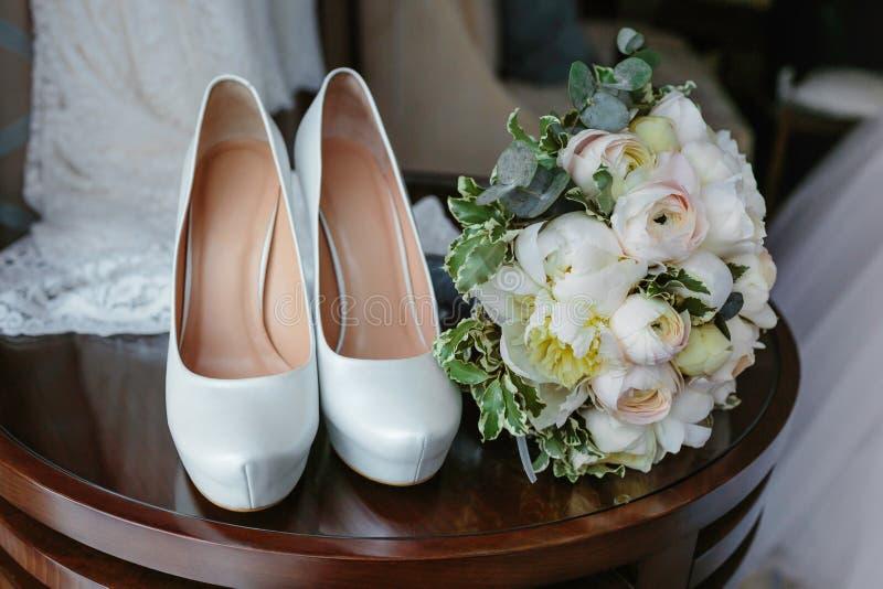 白玫瑰和典雅的婚礼鞋子花束在木桌上 免版税图库摄影