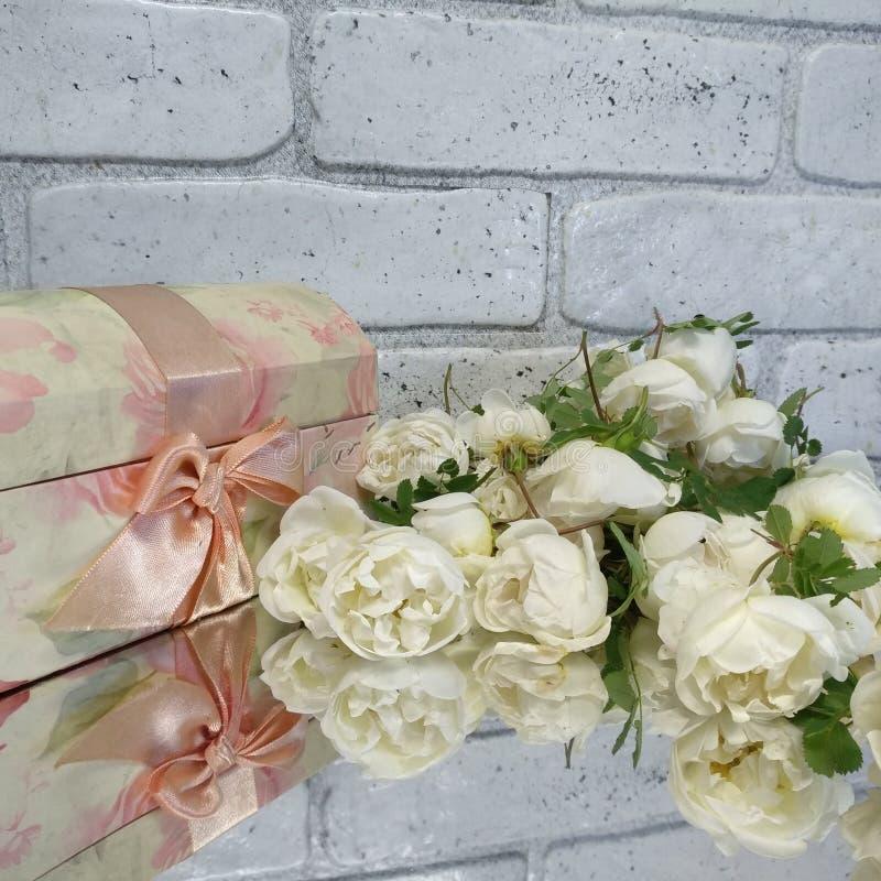 白玫瑰和桃红色葡萄酒首饰盒在灰色背景 免版税库存照片