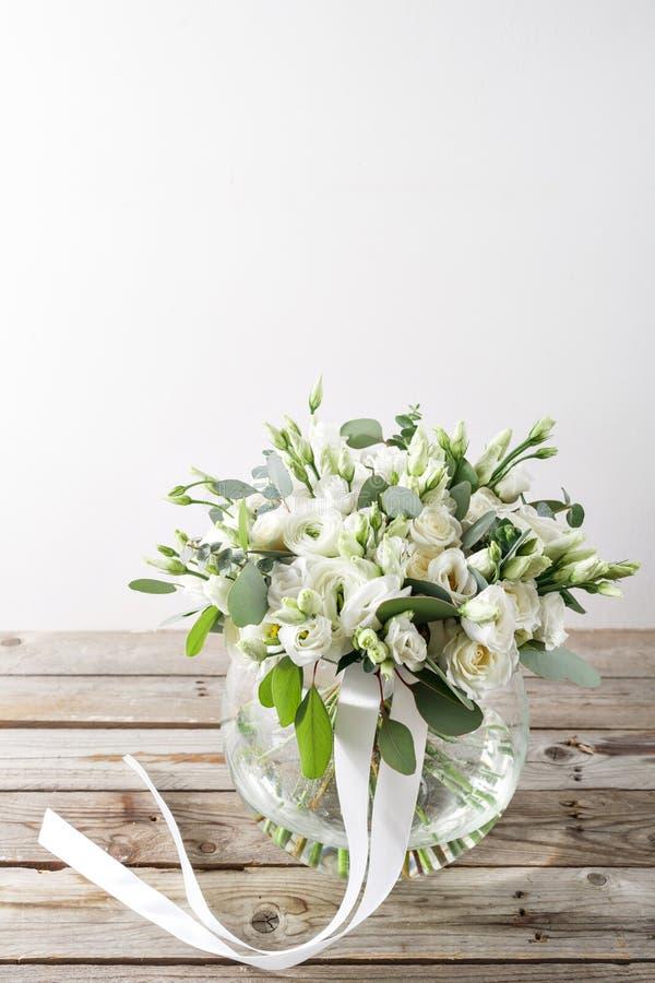 白玫瑰和毛茛婚礼花束在一张木桌上 老土气背景 库存照片