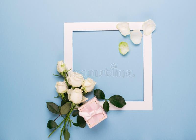 白玫瑰和白色框架礼物用在蓝色背景的新鲜的叶子装饰了 平的布局 复制空间 免版税库存图片