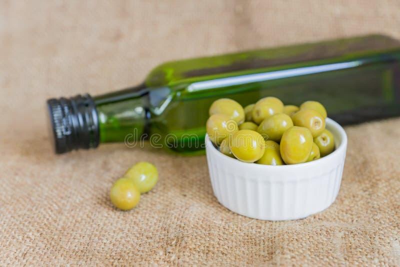 白瓷碗中鲜腌的绿色橄榄和粗布背景上的优质初榨橄榄油 库存照片