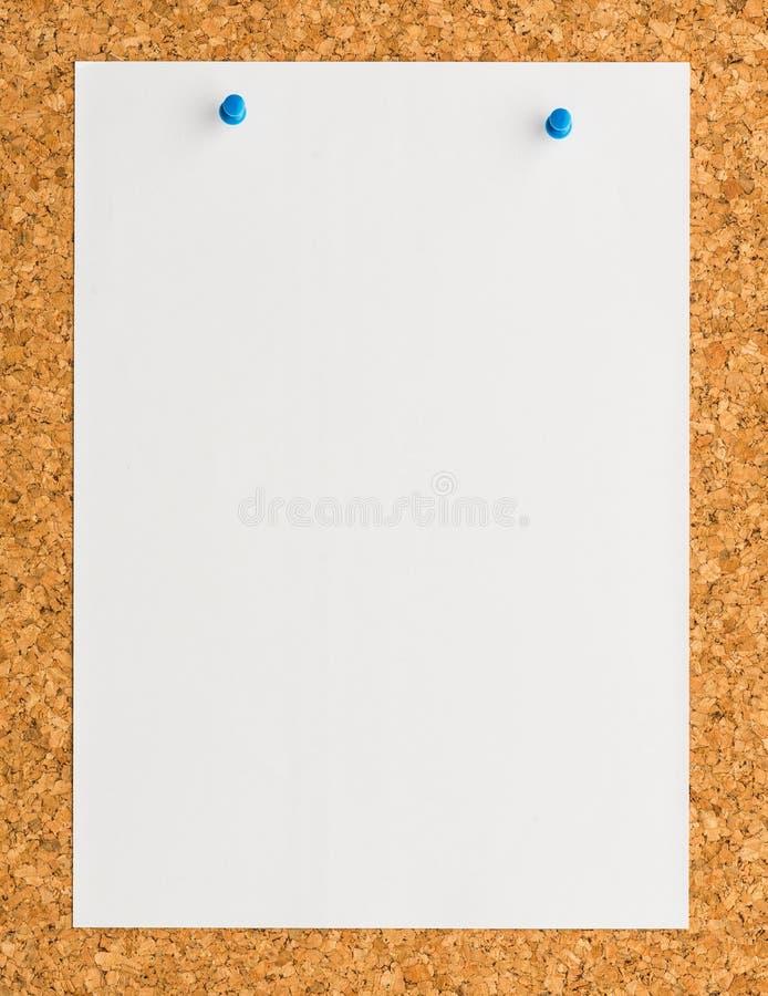 白皮书与蓝色推挤别针的笔记板料在黄柏板 库存图片