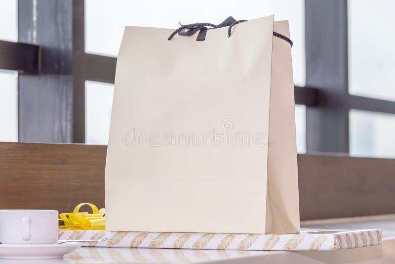 白皮书在桌和礼物安置的购物袋在windo附近 库存图片
