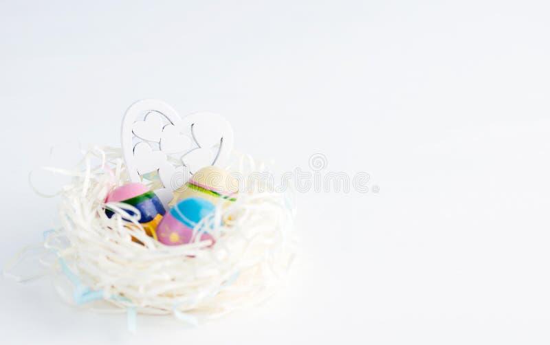 白皮书巢用三个葡萄酒复活节彩蛋和木心脏在蓝色背景 免版税库存照片
