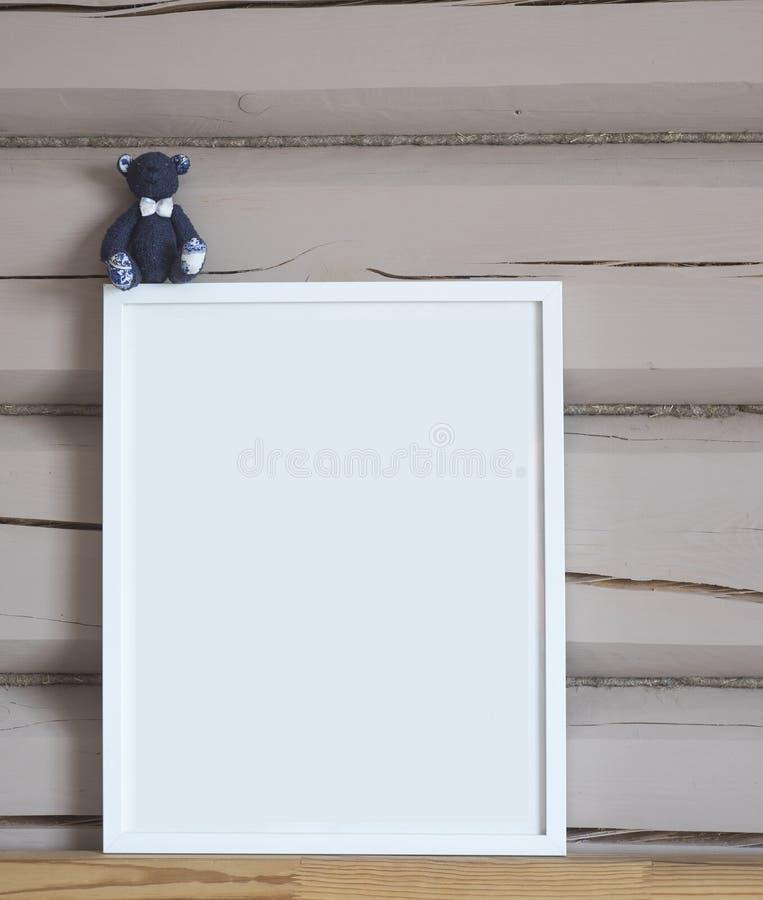 白皮书空白的内部海报,与蓝色熊玩具,被隔绝的垂直的嘲笑与在米黄木墙壁背景,孩子的框架 图库摄影