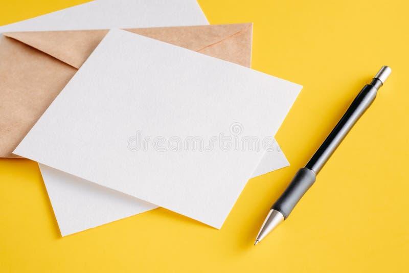 白皮书空的板料卡片、卡拉服特信封和笔在黄色背景 设计的大模型 免版税库存照片