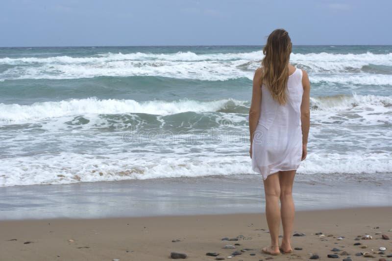 白着长袍的女孩观察风大浪急的海面 免版税图库摄影