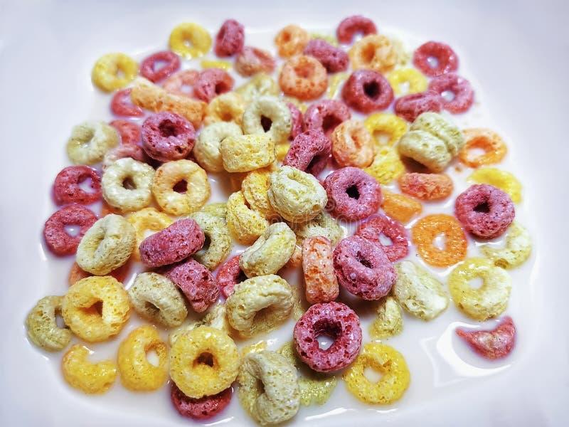 白碗中含牛奶的彩色环形果谷 免版税库存图片