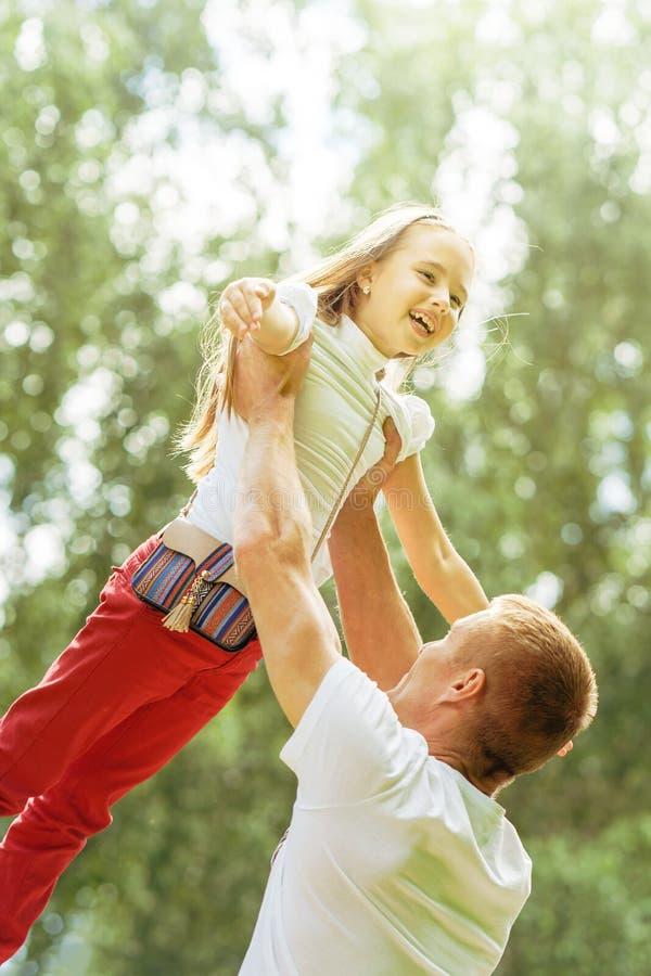 白种人一起使用在夏天公园的爸爸和年轻女儿 免版税库存图片