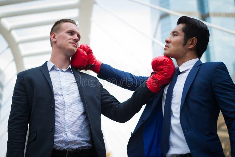 白种人与红色拳击手套战斗由上击的商人和亚洲商人对下巴 企业竞争的概念 免版税库存图片