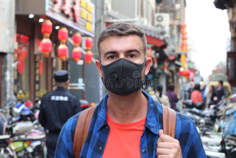 白种人人佩带的污染面具在亚洲 库存照片