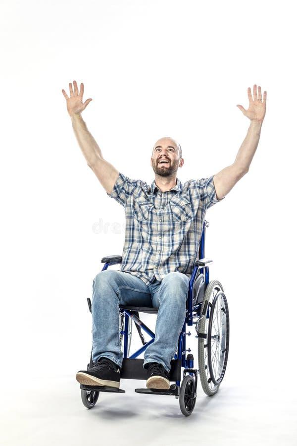 白种人人表示微笑和胳膊被伸出对天空,残疾在轮椅 免版税库存图片