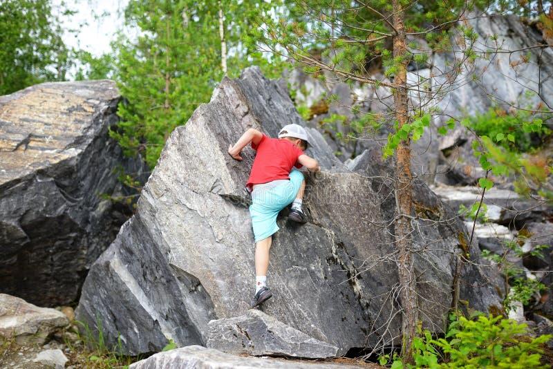 年轻白种人儿童男孩上升的岩石在森林里 免版税库存图片