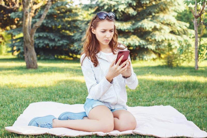 白种人十几岁的女孩谈话在细胞手机外面在公园 免版税库存照片